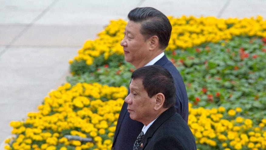 Philippine President Rodrigo Duterte, front, walks with Chinese President Xi Jinping during a welcome ceremony outside the Great Hall of the People in Beijing, China, Thursday, Oct. 20, 2016. (AP Photo/Ng Han Guan)