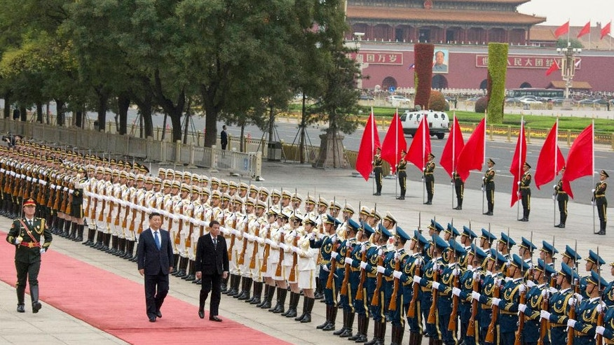 Philippine President Rodrigo Duterte, center, walks with Chinese President Xi Jinping during a welcome ceremony outside the Great Hall of the People in Beijing, China, Thursday, Oct. 20, 2016. (AP Photo/Ng Han Guan)