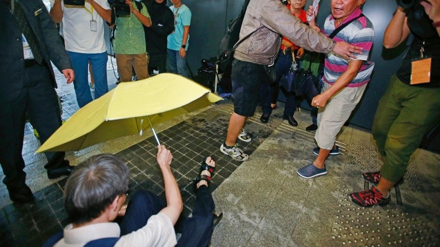 A pro-democracy protester, left, holding a yellow umbrella falls after scuffling with pro-Beijing supporters, right, outside the Legislative Council in Hong Kong, Wednesday, Oct. 19, 2016. Tensions flared at Hong Kong's legislature Wednesday as pro-Beijing lawmakers prevented a pair of newly elected representatives advocating independence for the Chinese region from getting a second chance at taking their oaths. (AP Photo/Kin Cheung)