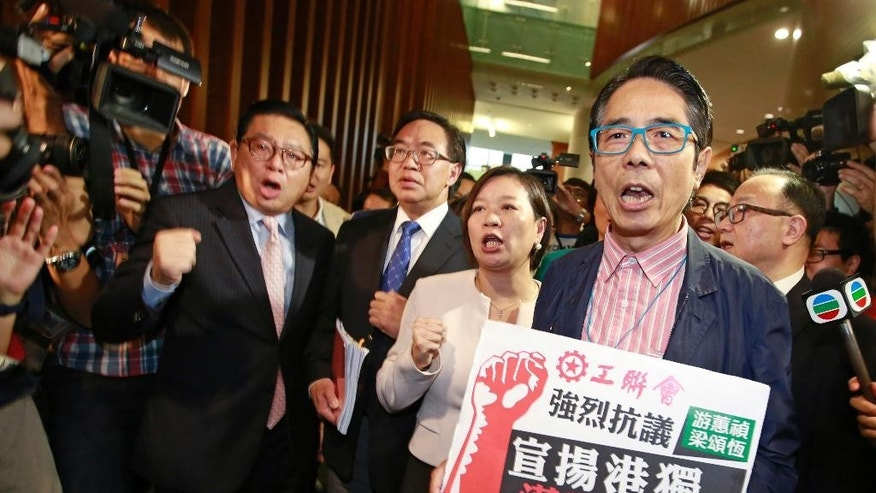 "Pro-Beijing lawmakers shout slogans after staging a walkout, depriving the Legislative chamber of the quorum needed to continue in Hong Kong, Wednesday, Oct. 19, 2016. Tensions flared at Hong Kong's legislature Wednesday as pro-Beijing lawmakers prevented a pair of newly elected representatives advocating independence for the Chinese region from getting a second chance at taking their oaths. The Chinese words on placard read ""Strongly protest against promoting Hong Kong Independence, disregarding the law."" (AP Photo/Kin Cheung)"