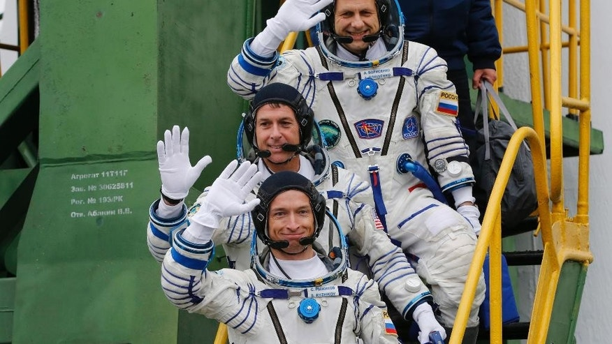 U.S. astronaut Shane Kimbrough, center, Russian cosmonauts Sergey Ryzhikov, bottom, and Andrey Borisenko, members of the main crew to the International Space Station (ISS), wave before boarding the Soyuz MS-02 space ship, in Russian leased Baikonur cosmodrome, Kazakhstan, on Wednesday, Oct. 19, 2016. (Maxim Shipenkov/Pool Photo via AP)