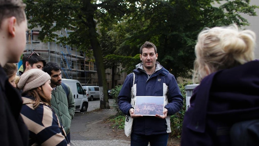 "In this photo taken Sunday, Oct. 9, 2016 refugee Firas Zakri from Syria, a tour guide of the so-called 'Refugee Tours' shows a photograph of his hometown Aleppo as he tours with a group of people through the district of Neukoelln in Berlin, Germany. Zakri is one of four refugee guides with ""querstadtein,"" or ""cross-city,"" a non-profit that initially started off offering tours of Berlin led by formerly homeless people. (AP Photo/Markus Schreiber)"