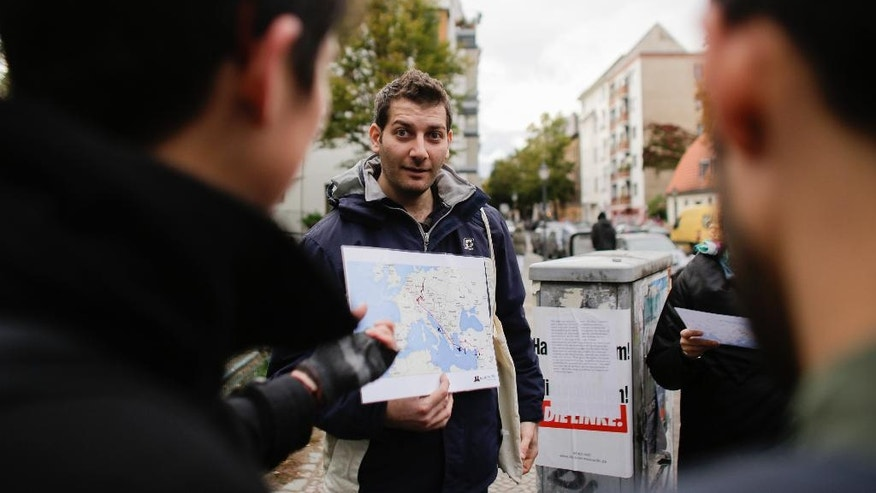 "In this photo taken Sunday, Oct. 9, 2016 refugee Firas Zakri from Syria, a tour guide of the so-called 'Refugee Tours' shows a map of Europe and the Mediterranean Sea as he tours with a group of people through the district of Neukoelln in Berlin, Germany. Zakri is one of four refugee guides with ""querstadtein,"" or ""cross-city,"" a non-profit that initially started off offering tours of Berlin led by formerly homeless people. (AP Photo/Markus Schreiber)"