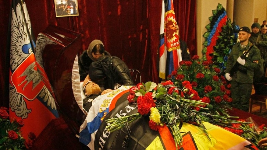 Mourners grieve at the coffin with the body of Arsen Pavlov, a senior commander of pro-Russia separatists in eastern Ukraine, during funeral in Donetsk, Ukraine, Wednesday, Oct. 19, 2016. Thousands have turned out to attend the funeral of one of top military chiefs of pro-Russia separatists in eastern Ukraine, who was killed in a bomb blast. The 33-year-old Arsen Pavlov, also known by nom de guerre Motorola, was killed Sunday when an unidentified explosive device went off in an elevator of his apartment building in Donetsk. (AP Photo/Alexander Ermochenko)