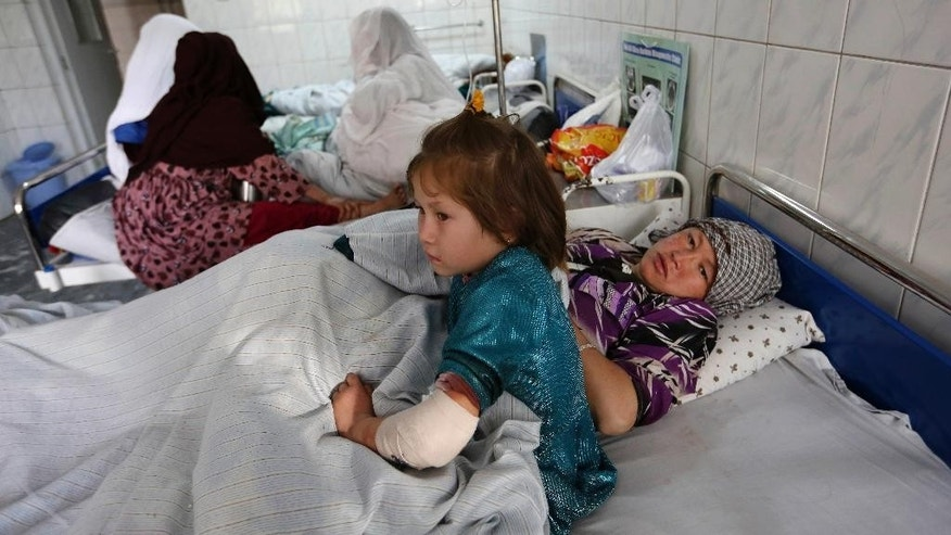 FILE - In this Wednesday, Oct. 12, 2016, file photo, Farida, 7, and her mother lay on the bed at a hospital after a militant attack on a Shiite shrine in Kabul, Afghanistan. The U.N. mission in Afghanistan says the number of children killed or wounded in the country's conflict has increased in the first nine months of 2016. UNAMA says in its third quarter report that out of a total of 2,461 children's casualties that the mission documented in 2016, there were 639 deaths and 1,822 wounded. That's a 15 percent increase, compared to the same period in 2015. (AP Photo/Rahmat Gul, File)