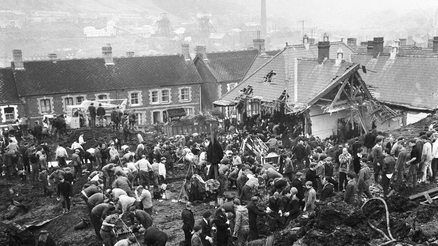 FILE - In this Oct. 22, 1966 file photo, rescue workers shovel the wet coal waste 28 hours after it slipped down the man-made mountain of coal waste and engulfed the Pantglas Junior School, and some houses, in Aberfan, Wales. Fifty years ago on Friday Oct. 21, 2016, an avalanche of mine waste swept down on a Welsh village and killed 116 children and 28 adults. Britain recalls the disaster that led to tougher rules on safety and fed a distrust of government that continues to this day. (AP Photo/File)