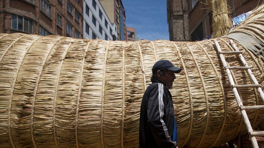 """American explorer Phil Buck walks past the reed boat named the """"Viracocha III,"""" and built by Bolivian Aymara Indians, in La Paz, Bolivia, Wednesday, Oct. 19, 2016. Buck is preparing to cross the Pacific Ocean from South America to Australia in the Viracocha III, a  three-masted boat that was made from several tons of dried reeds of the totora plant. The expedition seeks to prove that ancient mariners could have made such journeys across huge ocean expanses in reed ships, and that such vessels could have been a factor in human migration. (AP Photo/Juan Karita)"""
