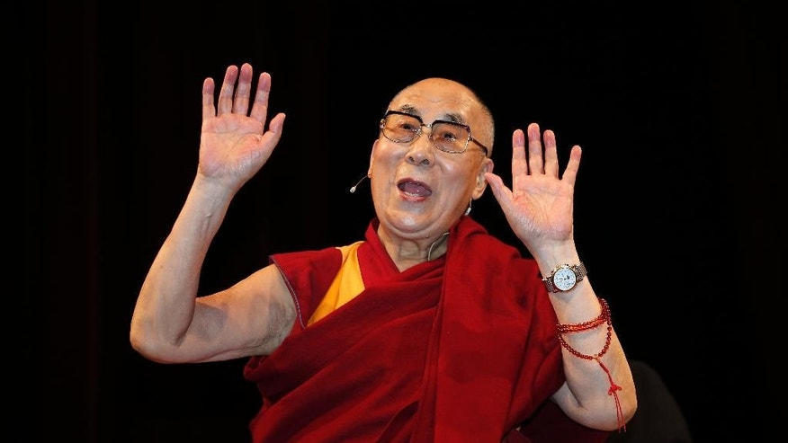 The Dalai Lama Tenzin Gyatso acknowledges the crowd at the Arcimboldi Theater where he was conferred with the honorary citizenship of the city of Milan, in Milan, Italy, Thursday, Oct. 20, 2016. The Chinese Embassy in Rome has strongly protested plans by Milan city council to bestow honorary citizenship Thursday on the Dalai Lama, saying it would have a negative impact on bilateral relations and regional cooperation. (AP Photo/Antonio Calanni)