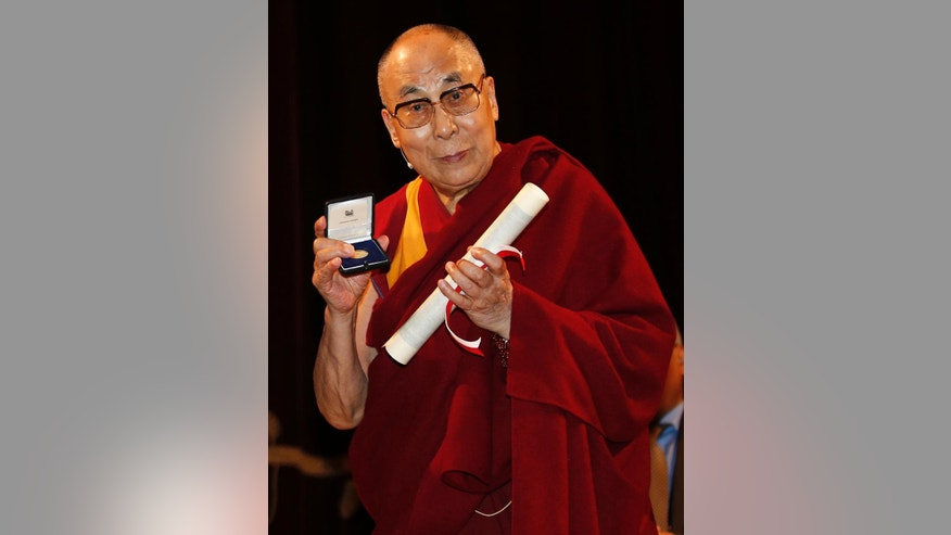 The Dalai Lama Tenzin Gyatso holds his honorary citizenship certificate, at the Arcimboldi Theater, in Milan, Italy, Thursday, Oct. 20, 2016. The Chinese Embassy in Rome has strongly protested plans by Milan city council to bestow honorary citizenship Thursday on the Dalai Lama, saying it would have a negative impact on bilateral relations and regional cooperation. (AP Photo/Antonio Calanni)