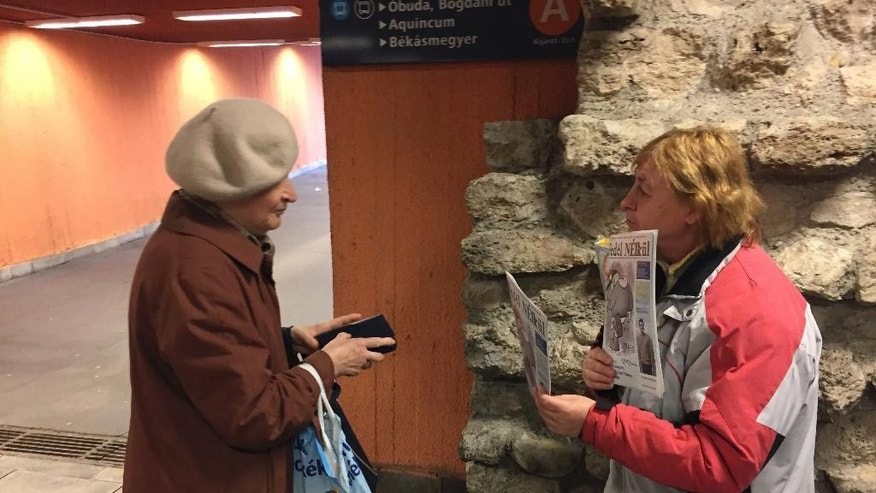 "A woman buys a magazine from homeless Erika Szuhogyi, right, in Budapest, Hungary, Thursday, Oct. 20, 2016. Reporters and editors from Nepszabadsag, whose suspension earlier this month has raised concerns about media pluralism, wrote articles for ""Without A Roof"" and helped homeless to sell the biweekly publication, talking with buyers about Hungarian media matters. (AP Photo/Andras Nagy)"