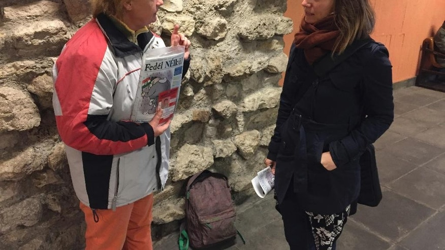 "Homeless Erika Szuhogyi, left, talks to journalist Csilla Urban who helps her selling magazines in Budapest, Hungary, Thursday, Oct. 20, 2016. Reporters and editors from Nepszabadsag, whose suspension earlier this month has raised concerns about media pluralism, wrote articles for ""Without A Roof"" and helped homeless to sell the biweekly publication, talking with buyers about Hungarian media matters. (AP Photo/Andras Nagy)"