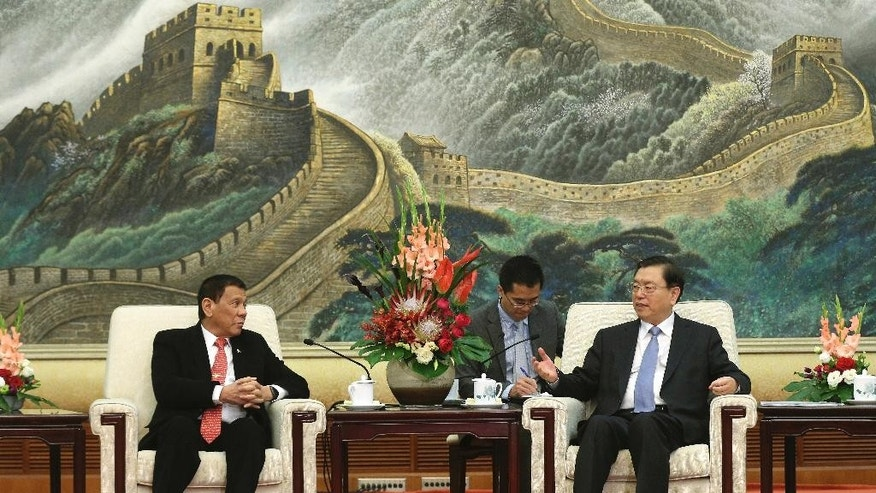 Philippines President Rodrigo Duterte, left, listens to Zhang Dejiang, chairman of the Standing Committee of the National People's Congress of China, during a meeting at the Great Hall of the People in Beijing Thursday, Oct. 20, 2016. China and the Philippines have agreed to resume a dialogue on their dispute over the South China Sea, a senior Chinese diplomat said Thursday following talks between the countries' leaders. (Wu Hong/Pool Photo via AP)