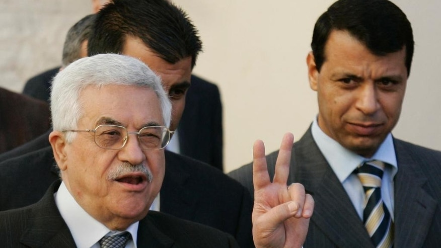 FILE - in this Dec. 18, 2006 file photo, Palestinian Authority President Mahmoud Abbas, left, flashes the V-sign as then Fatah leader, Mohammed Dahlan, looks on in the West Bank town of Ramallah. Senior officials say Palestinian President Mahmoud Abbas is pushing for leadership elections in his Fatah movement and the PLO before the end of the year, as part of an attempt to block the return of exiled rival Mohammed Dahlan. Abbas has come under growing pressure from Arab states to take back Dahlan, a former top aide and millionaire businessman who in exile forged close ties with leaders of Egypt, the United Arab Emirates and other countries in the region. (AP Photo/Kevin Frayer, File)