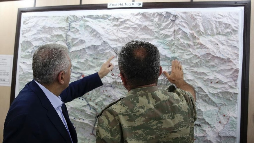 FILE - In this Monday, Sept. 5, 2016 file photo, an army commander informs Turkey's Prime Minister Binali Yildirim, left, on a Turkey-Iraq border map, in Cukurca, Turkey. Just days into the operation to retake the Islamic State-held city of Mosul, a fault-line has widened between Iraq and Turkey that reflects the lingering distrust of the various forces arrayed against the extremists. The rhetoric is growing increasingly heated on both sides, with some hinting at an open confrontation after the city is liberated – or maybe even before. (Prime Ministry Press Service, Pool photo via AP, File)