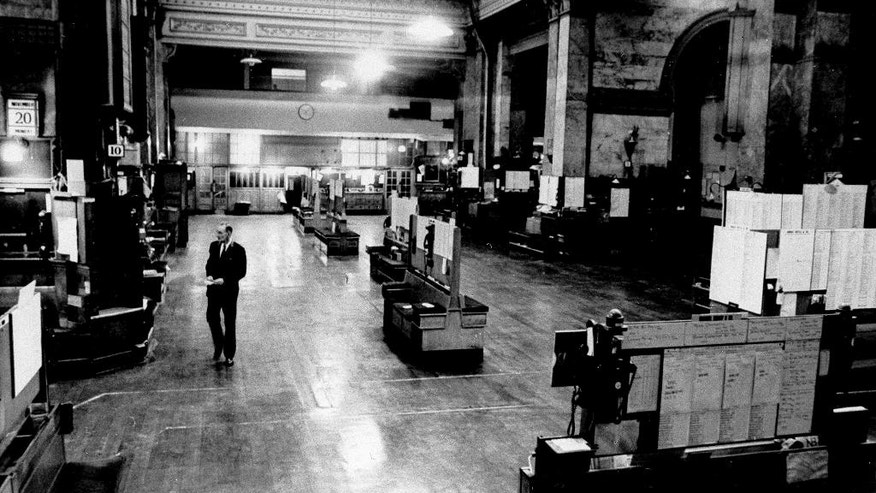 FILE - In this Nov. 20, 1967 file photo, a lone stock exchange messenger walks across the deserted floor of the London Stock Exchange the morning after a royal proclamation ordered the building closed to avoid wild dealing in the market after the devaluation of the pound. The closure was made to avoid a repetition of the confusion of the last devaluation in 1949.  The pound has endured a similar devaluation since the country voted to leave the European Union in a referendum in June. (AP Photo/File)