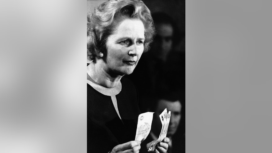 "FILE - In this April 30, 1976 file photo, Conservative Party leader Margaret Thatcher holding up five one-pound notes during a speech in Finchley, North London. ""Every time you spend five pounds,"" she said, ""the Government owes one to creditors abroad."" The pound has endured a similar devaluation since the country voted to leave the European Union in a referendum in June 23, 2016. (AP Photo, File)"