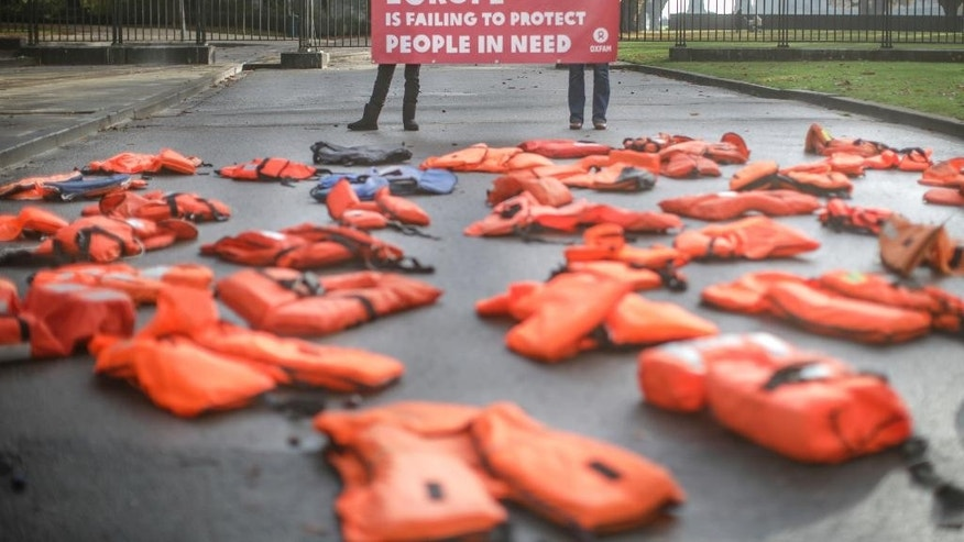 Protestors display lifejackets as they demonstrate outside an EU summit venue in Brussels, Thursday, Oct. 20, 2016. EU leaders begin a two day meeting Thursday to discuss migration and trade. (AP Photo/Olivier Matthys)