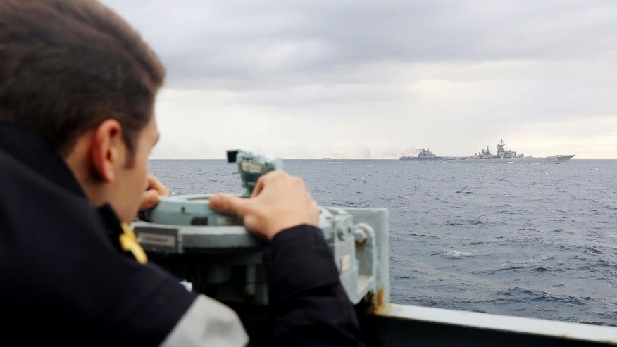"This is a handout photo issued by Britain's  Ministry of Defence and taken on Tuesday Oct 18, 2016 of a Royal Navy lookout onboard HMS Richmond, observing Russian aircraft carrier Admiral Kuznetsov, rear second right, and Russian Battlecruiser Pyotr Velikiy on the right,   which are part of a Russian task group during its transit through the North Sea.  Britain is sending warships to watch a Russian aircraft carrier group and other vessels as they sail through the North Sea and the English Channel. Defense Secretary Michael Fallon says that the military will watch the ""every step of the way.'' (PO(Phot) Dez Wade/MoD/Crown Copyright via AP)"