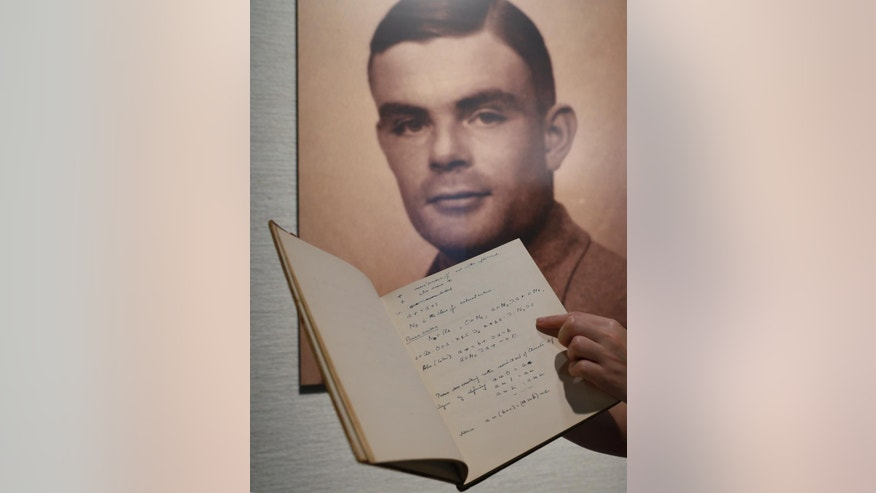 March 19, 2015: A page from the notebook of Alan Turing, the World War II code-breaking genius, is displayed in front of his portrait at an auction preview in Hong Kong.