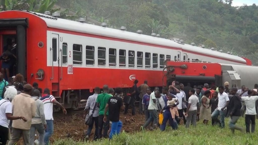 In this image made from video, people walk beside a derailed train carriage after an accident in Eseka, Cameroon, Friday, Oct. 21, 2016. Cameroon's transport minister says at least 53 people have died after a train overloaded with passengers derailed along the route that links the country's two major cities. (Equinox TV via AP)