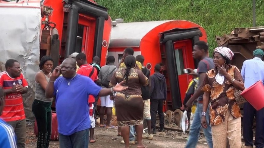 In this image made from video, passengers stand beside derailed train carriages after an accident in Eseka, Cameroon, Friday, Oct. 21, 2016. Cameroon's transport minister says at least 53 people have died after a train overloaded with passengers derailed along the route that links the country's two major cities. (Equinox TV via AP)