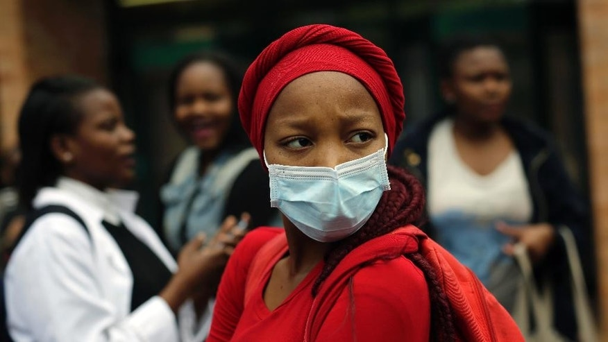 A medical students stares at a line of security officers at the University of the Witwatersrand's medical school in Johannesburg, South Africa, Friday, Oct. 21 2016. Protests calling for free education have sometimes turned violent and have affected  many South African universities since last month. (AP Photo/Jerome Delay)