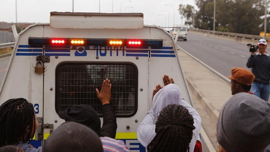 Students from the University of Western Cape campus slam their hands on a police truck as they protest near the Bellville Magistrate's Court, walking back to their campus on the outskirts of Cape Town, South Africa, Friday, Oct. 21, 2016. A group of students appeared in the Bellville Magistrate's Court after being arrested during recent violent protest calling on free education in South Africa. (AP Photo/Schalk van Zuydam)