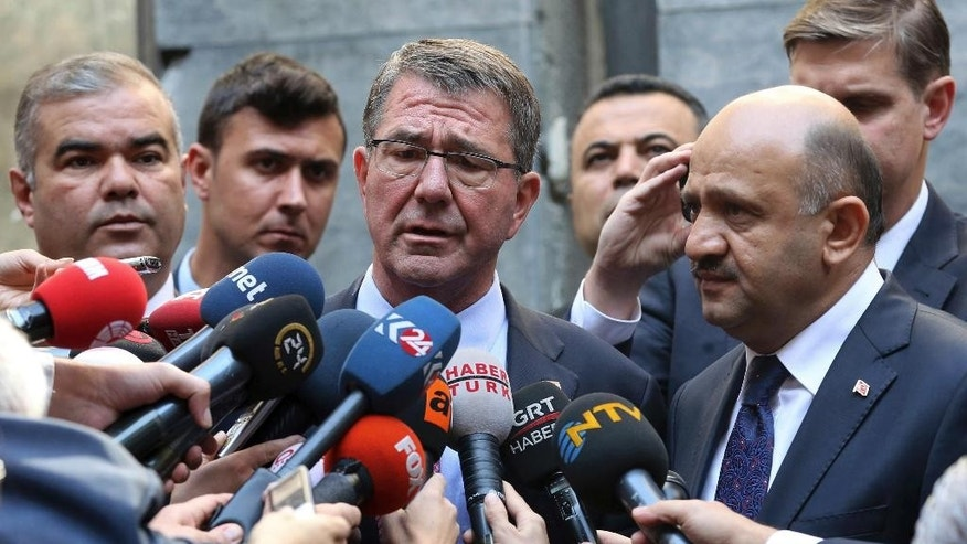 U.S Secretary of Defense Ash Carter, center, speaks to the media after he left flowers near the damaged section of the Turkish parliament bombed during the July 15 failed coup, in Ankara, Turkey, Friday, Oct. 21, 2016. Carter met with President Recep Tayyip Erdogan and other top leaders and defense officials in Ankara amid escalating tensions between Turkey and Iraq over Turkish military operations in northern Iraq as allied forces move to retake Mosul from Islamic State militants. (Adem Altan/Pool Photo via AP)