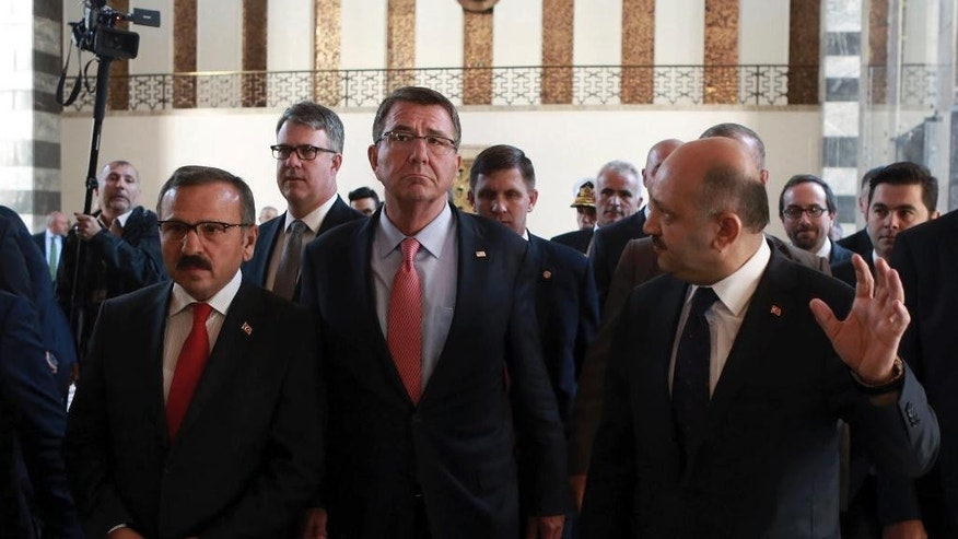 U.S Secretary of Defense Ash Carter, center, speaks to his Turkish counterpart Fikri Isik as he visits Turkish parliament in Ankara, Turkey, Friday, Oct. 21, 2016. Carter met with President Recep Tayyip Erdogan and other top leaders and defense officials in Ankara amid escalating tensions between Turkey and Iraq over Turkish military operations in northern Iraq as allied forces move to retake Mosul from Islamic State militants. (Adem Altan/Pool Photo via AP)