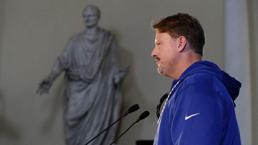 New York Giants head coach Ben McAdoo answers questions from journalists next to a statue of a Roman Magistrate from 1st century AD, during a press conference at Syon House in Syon Park, south west London, Friday, Oct. 21, 2016. The Los Angeles Rams are due to play the New York Giants at Twickenham stadium in London on Sunday in a regular season NFL game. (AP Photo/Matt Dunham)