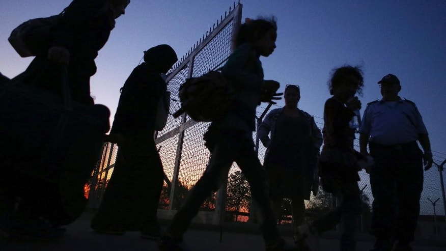 Migrants from Syria walk into a refugee camp in Kokkinotrimithia village outside the capital Nicosia, Cyprus, Friday, Oct. 21, 2016.  A Cyprus police spokesman says a boat with 83 people aboard including 37 children has been towed to a harbor on the east Mediterranean island's northwestern coast. (AP Photo/Petros Karadjias)