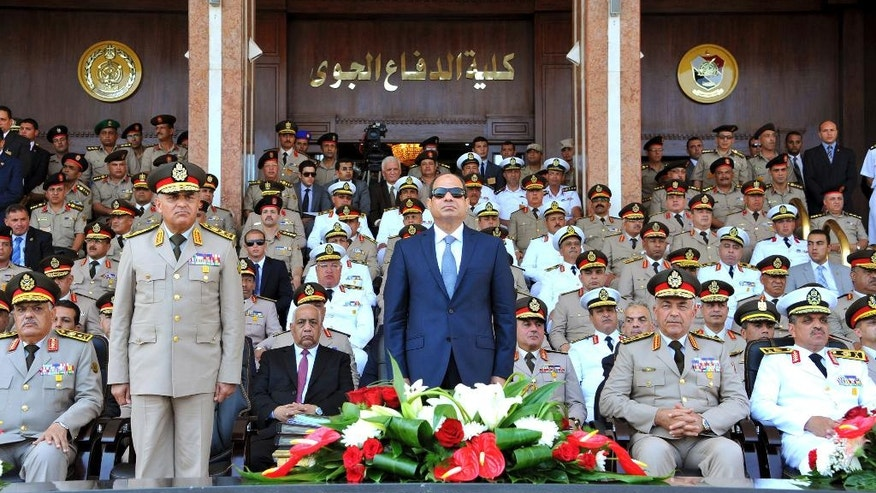 FILE - In this July 22, 2015, file photo, provided by the office of the Egyptian Presidency, Egyptian President Abdel-Fattah el-Sissi, center, and Defense Minister Sedqi Sobh, left, stand at attention, at the Air Defense Academy in Alexandria. Egypt has made fighting Islamic militants its overriding foreign policy objective, a decision that led to a series of regional realignments that have puzzled Western backers, antagonized traditional Arab allies like Saudi Arabia and brought Cairo closer to Syrian President Bashar Assad, Russia and Iran. (Mohammed Samaha/Egyptian Presidency via AP, File)