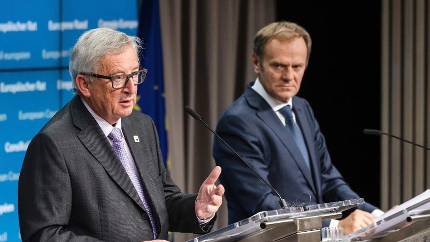 European Commission President Jean-Claude Juncker, left, and European Council President Donald Tusk address the media after the first day of an EU summit in Brussels early Friday, Oct. 21, 2016. European Union leaders pledged early Friday to keep all options open to respond to any atrocities committed by President Bashar Assad's regime and his Russian backers in Syria but stopped short of threatening to impose sanctions. (AP Photo/Geert Vanden Wijngaert)