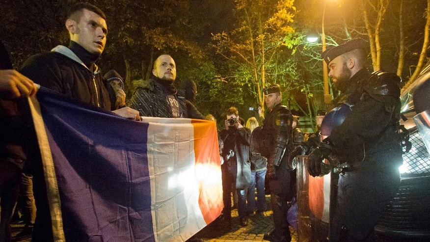 Police officers hold the French national flag as they face riot police officers next to the Elysee Palace, the residence and office of French President Francois Hollande, in a rally to protest their working condition at the Champs Elysee avenue in Paris, France, Friday, Oct. 21, 2016. 500 police officer went to the street to protest the lack of equipment and rising anti-police violence in France. (AP Photo/Michel Euler)
