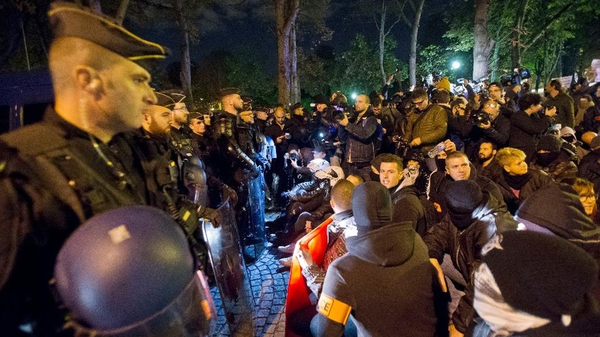 Police officers stage a sit-in as they face riot police officers next to the Elysee Palace, the residence and office of French President Francois Hollande, in a rally to protest their working condition at the Champs Elysee avenue in Paris, France, Friday, Oct. 21, 2016. 500 police officer went to the street to protest the lack of equipment and rising anti-police violence in France. (AP Photo/Michel Euler)