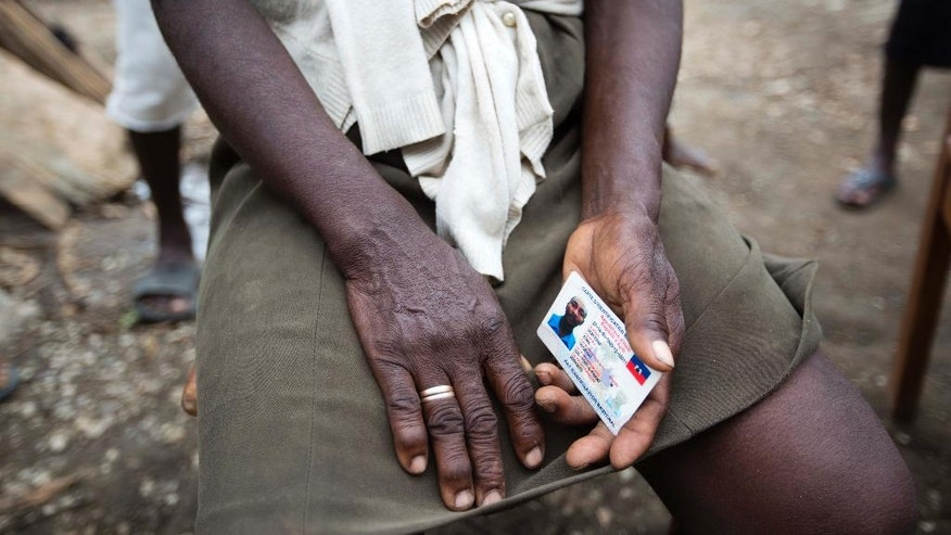 In this Tuesday, Oct. 18, 2016 photo, Bertha Mesilier holds the national identification card of her missing husband Edma Desravine, who was last seen seeking refuge from the heavy rainfall and winds brought by Hurricane Matthew, in Port-a-Piment, a district of Les Cayes, Haiti.Nobody has seen or heard from the 71-year-old grandfather known for his sly sense of humor and bad luck at cock fights, in the 2 ½ weeks since Hurricane Matthew sent floodwaters and debris crashing into his riverside shantytown.(AP Photo/Dieu Nalio Chery)