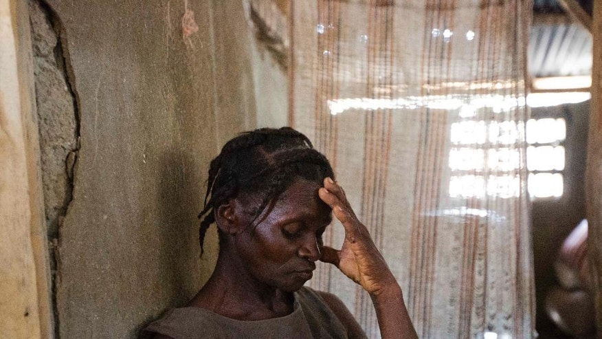 In this Tuesday, Oct. 18, 2016, Bertha Mesilier leans against a wall in the room she shared with her now missing husband Edma Desravine, who was last seen seeking refuge from the heavy rainfall and winds brought by Hurricane Matthew, in Port-a-Piment, a district of Les Cayes, Haiti. Family and neighbors near the town of Port-a-Piment have dug by hand through wreckage and scoured the riverbanks, but to no avail. (AP Photo/Dieu Nalio Chery)