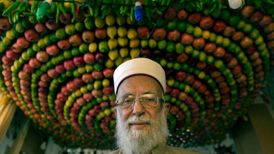 In this Sunday, Oct. 16, 2016 photo, the high priest of the ancient Samaritan community Abdullah Wasef Tawfiq poses for a photo inside his house, during their celebrations of the week-long biblical holiday of Sukkot, or Feast of Tabernacles, on Mount Gerizim, overlooking the West Bank city of Nablus. In the Bible, God commands the people of Israel to build huts symbolizing the Israelites' encampments as they wandered the desert following the exodus from Egypt. Unlike the outdoor huts Jews construct on the holiday, Samaritans build exquisite canopies of densely packed fruit, which are attached to metal frames and perched on stilts or suspended from living room ceilings. (AP Photo/Nasser Nasser)