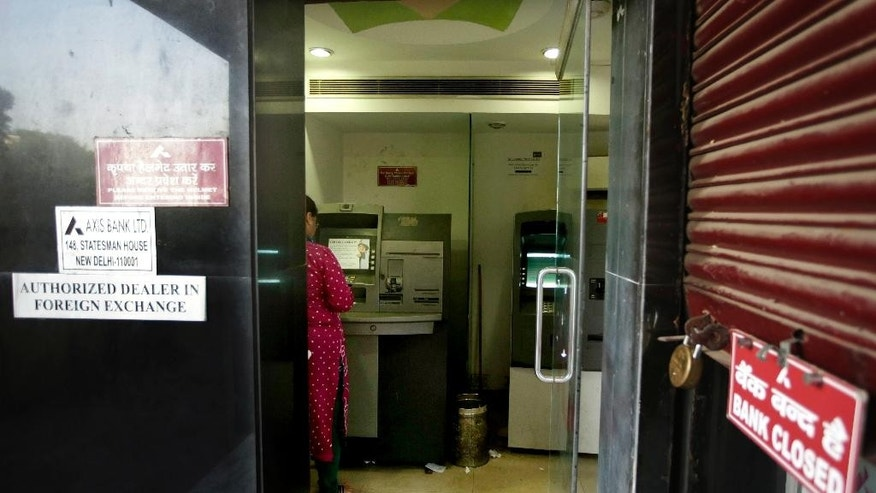 An Indian woman uses an ATM in New Delhi, India, Friday, Oct. 21, 2016. Indian banks are scrambling to contain the damage after more than 3.2 million debit cards were feared to have been hacked. (AP Photo/Altaf Qadri)