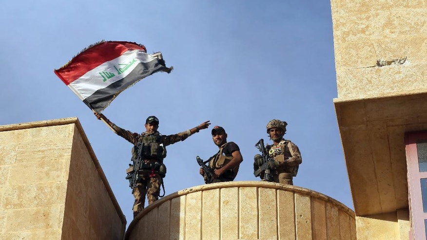 Iraq's elite counterterrorism forces raise an Iraqi flag after retaking Bartella, outside Mosul, Iraq, Friday, Oct. 21, 2016. Iraqi and Kurdish forces backed by a U.S.-led coalition launched a multi-pronged assault this week to retake Mosul and surrounding areas from Islamic State militants. The operation is the largest undertaken by the Iraqi military since the 2003 U.S.-led invasion. Iraqi officials said they had advanced as far as the town of Bartella, 15 kilometers (nine miles) from Mosul's outskirts, by Thursday. (AP Photo/ Khalid Mohammed)