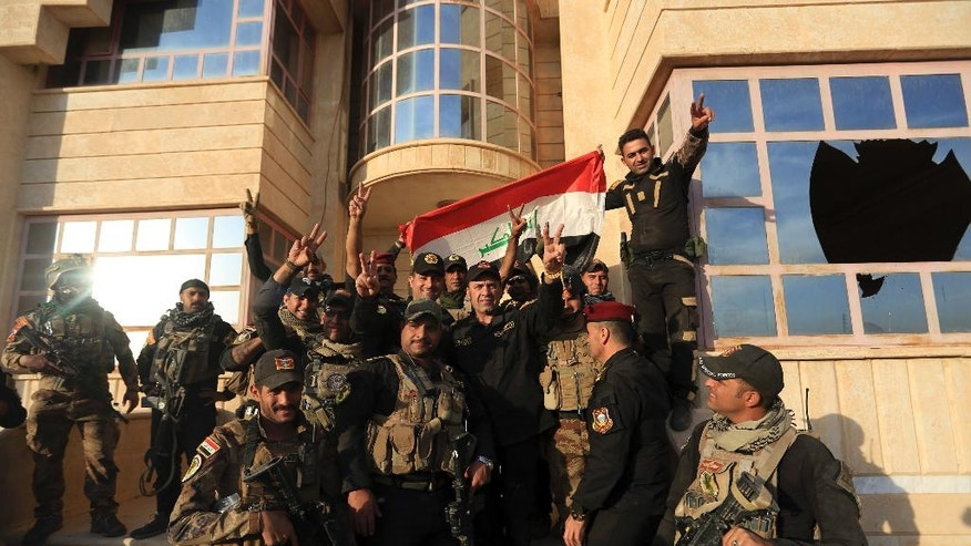 Iraq's elite counterterrorism forces celebrate after retaking Bartella, outside Mosul, Iraq, Friday, Oct. 21, 2016. Iraqi and Kurdish forces backed by a U.S.-led coalition launched a multi-pronged assault this week to retake Mosul and surrounding areas from Islamic State militants. The operation is the largest undertaken by the Iraqi military since the 2003 U.S.-led invasion. Iraqi officials said they had advanced as far as the town of Bartella, 15 kilometers (nine miles) from Mosul's outskirts, by Thursday. (AP Photo/ Khalid Mohammed)