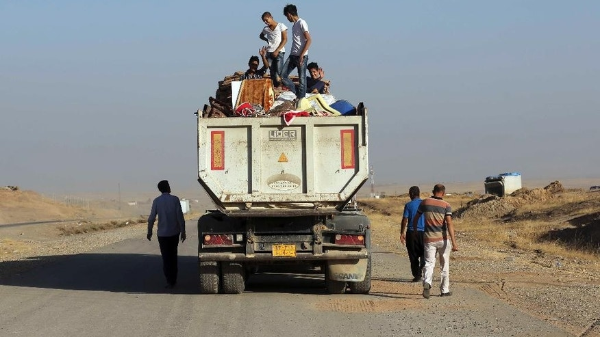Iraqi displaced people, whose villages was liberated recently,  return with their furniture, outside Mosul, Iraq, Thursday, Oct. 20, 2016.  In a significant escalation of the battle for Mosul, elite Iraqi special forces joined the fight Thursday, unleashing a pre-dawn assault on an Islamic State-held town east of the besieged city. (AP Photo/ Khalid Mohammed)