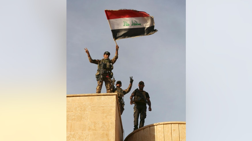 Iraq's elite counterterrorism forces raise an Iraqi flag after retaking Bartella, outside Mosul, Iraq, Friday, Oct. 21, 2016. Iraqi and Kurdish forces backed by a U.S.-led coalition launched a multi-pronged assault this week to retake Mosul and surrounding areas from IS. The operation is the largest undertaken by the Iraqi military since the 2003 U.S.-led invasion. Iraqi officials said they had advanced as far as the town of Bartella, 15 kilometers (nine miles) from Mosul's outskirts, by Thursday. (AP Photo/ Khalid Mohammed)
