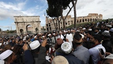 Muslim men gather for a prayer and demonstration near Rome's ancient Colosseum, seen in the background Friday, Oct. 21, 2016. The Muslim community of Rome gathered by the Colosseum to pray and demonstrate against the alleged shutting down by police of unofficial places of worship in the city.  (AP Photo/Alessandra Tarantino)