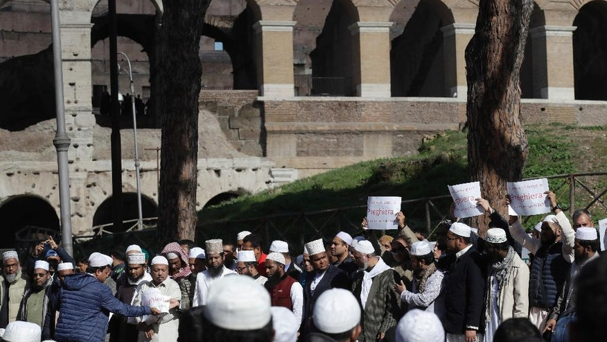 """Men hold up signs reading in Italian """"To close a place of worship is against faith"""" during a demonstration near Rome's ancient Colosseum, seen in the background, Friday, Oct. 21, 2016. The Muslim community of Rome gathered by the Colosseum to demonstrate against the alleged shutting down by police of unofficial places of worship in the city.  (AP Photo/Alessandra Tarantino)"""