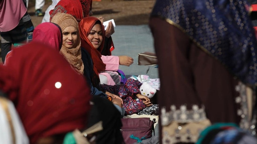 Women sit on the women's side during Friday prayers and a demonstration near Rome's ancient Colosseum, Friday, Oct. 21, 2016. The Muslim community of Rome gathered by the Colosseum to pray and demonstrate against the alleged shutting down by police of unofficial places of worship in the city.  (AP Photo/Alessandra Tarantino)
