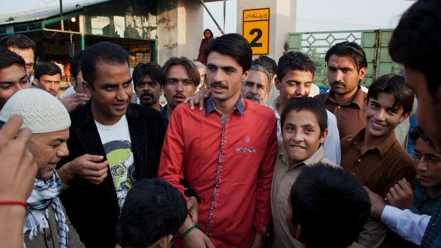 Pakistani tea vendor Arshad Khan, 18, center, is surrounded by shopkeepers and colleagues at a market where he sells tea in Islamabad, Pakistan, Friday, Oct. 21, 2016. Khan, who saw his life change overnight after a picture of him at work went viral, said Friday he was totally unaware of social media until recently when boys and girls suddenly started thronging a flea market in Islamabad to take selfies with him.(AP Photo/B.K. Bangash)