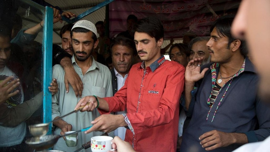Pakistani tea vendor Arshad Khan, 18, center, prepares tea at a stall in a market in Islamabad, Pakistan, Friday, Oct. 21, 2016. Khan, who saw his life change overnight after a picture of him at work went viral, said Friday he was totally unaware of social media until recently when boys and girls suddenly started thronging a flea market in Islamabad to take selfies with him.(AP Photo/B.K. Bangash)