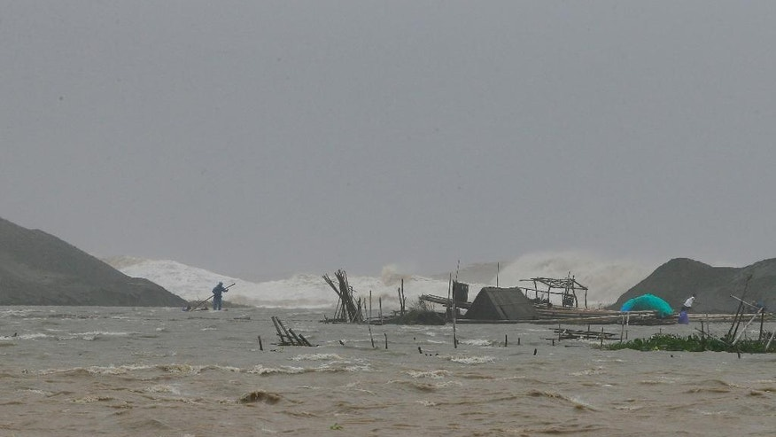 A fisherman works on his destroyed fish cages amidst huge waves brought about by Super Typhoon Haima that lashes Vigan township, Ilocos Sur province in northern Philippines Thursday, Oct. 20, 2016. Super Typhoon Haima slammed into the northeastern Philippine coast late Wednesday with ferocious winds and rain that rekindled fears and memories from the catastrophe wrought by Typhoon Haiyan in 2013. (AP Photo/Bullit Marquez)