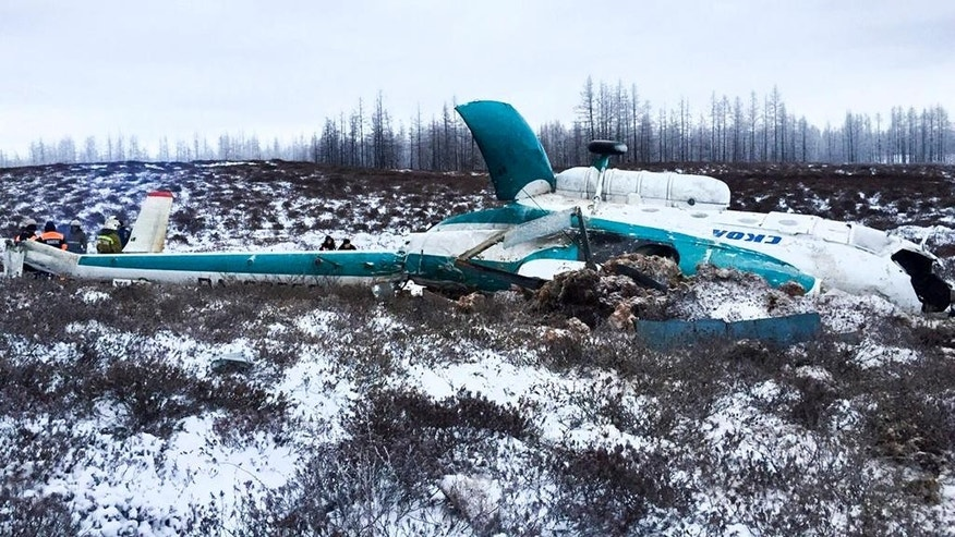 In this handout photo, made available by Russian Emergency Situations Ministry, Saturday, Oct. 22, 2016, a Mi-8 helicopter lies on the ground after it crashed about 45 kilometers (28 miles) northeast of Staryi Urengoi in Hassana, Russia. Russia's aviation agency says 19 people have died after a helicopter carrying oil workers crashed. (Russian Ministry for Emergency Situations photo via AP)